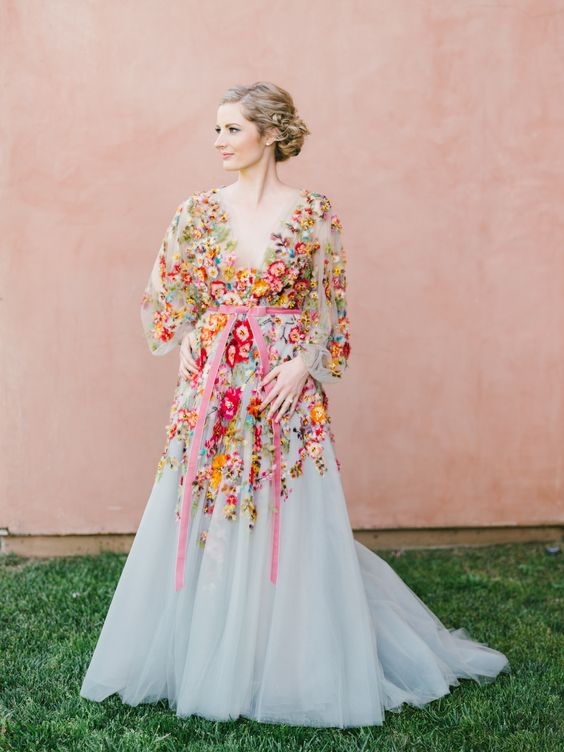 a blush A-line wedding dress with colorful floral embroidery, a plunging neckline, long sleeves and a pink sash for a garden wedding
