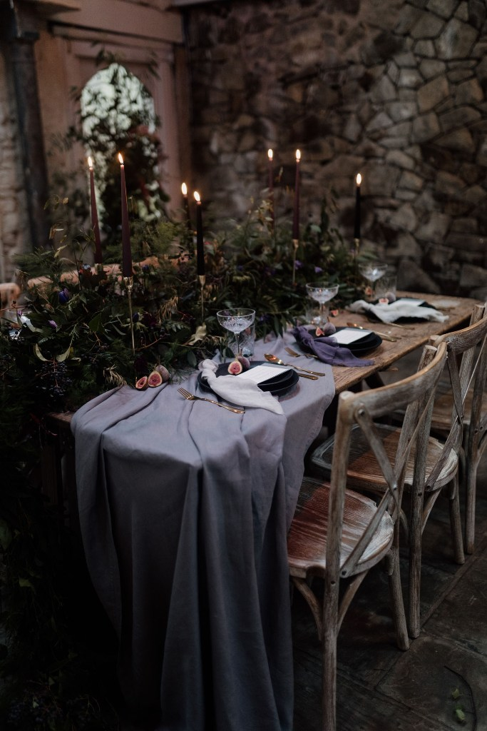 The wedding reception table was done with a lilac runner, purple napkins, lush greenery and purple blooms