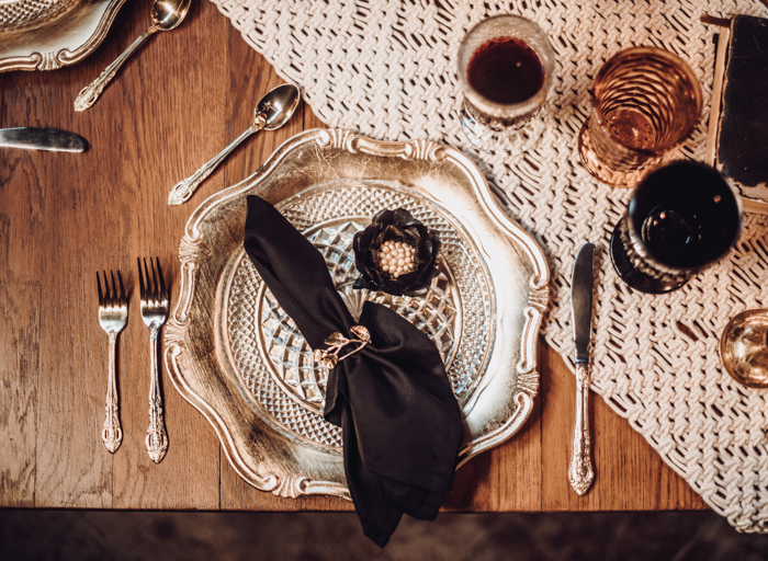 The wedding tablescape was decorated with a macrame runner, silver chargers, black linens and silver cutlery