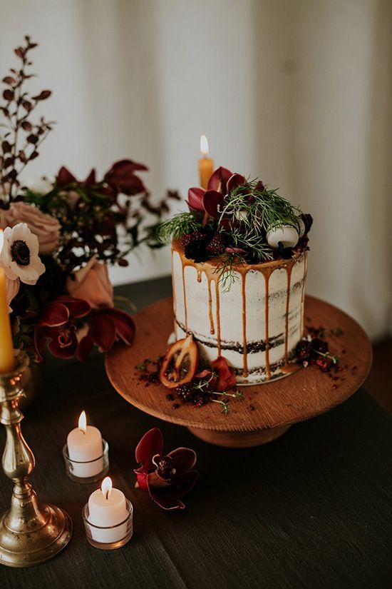 a chocolate naked wedding cake with caramel drip, fresh berries and dark blooms, macarons and greenery