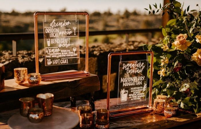 The wedding decor was done with copper signs, candles and bold blooms