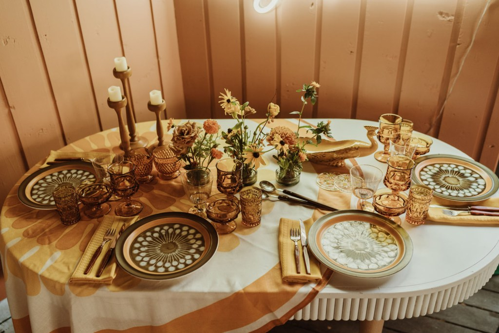 The wedding tablescape was done with a printed tablecloth, bold plates and amber glasses, candles in wooden candleholders and bold blooms