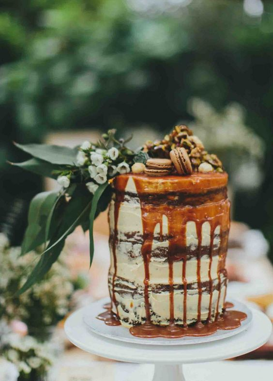 a chocolate naked wedding cake with caramel drip, macarons, nuts, greenery and white blooms is amazing