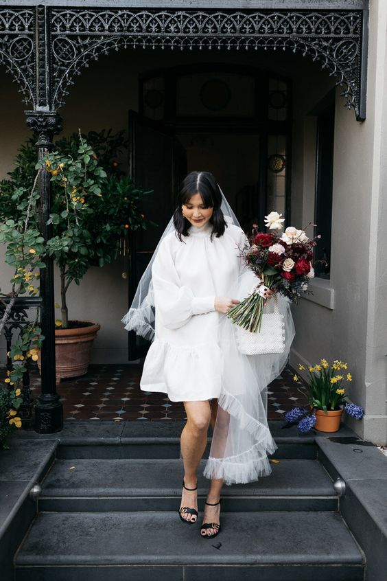 a short A-line wedding dress with a turtleneck and puff sleeves, black heels and a veil for a retro look