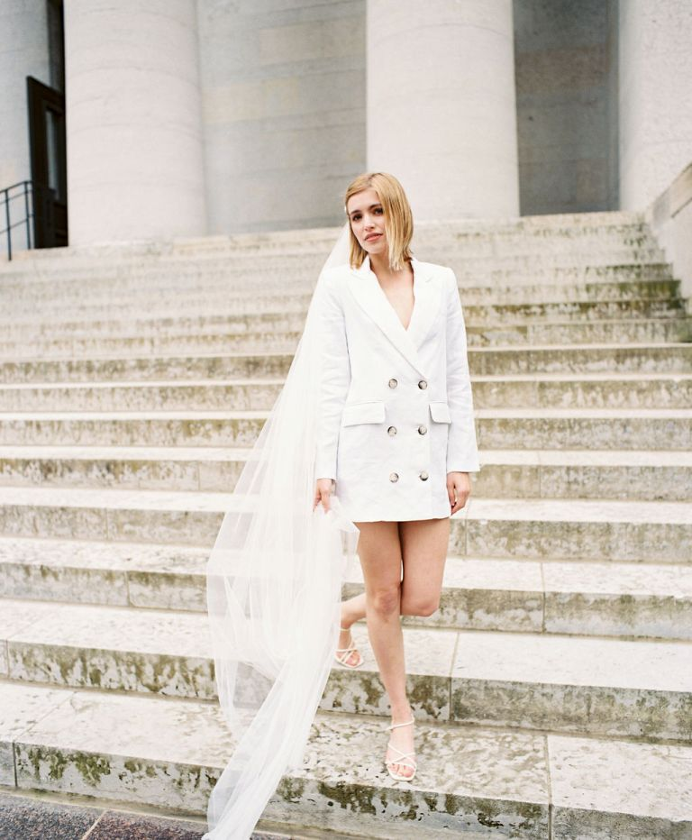 a short white blazer wedding dress, strappy heels and a long veil for an ultra-modern bridal look