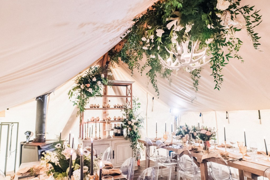The wedding reception space was done with lush greenery and white blooms, antler chandeliers, black candles and neutral linens