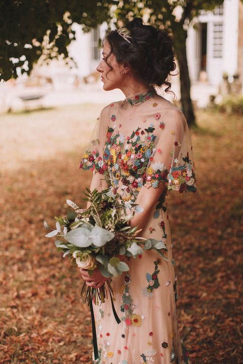 a cool sheath wedding dress with colorful floral embroidery, a high neckline and short sleeves for a bloom-loving bride
