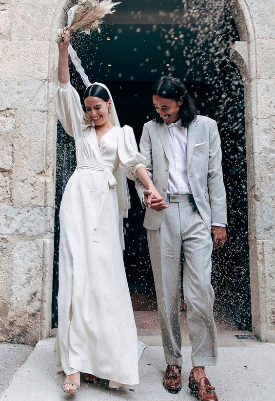 a chic casual wrap wedding dress with puff sleeves and a train plus grey heels and a veil for a stylish wedding look
