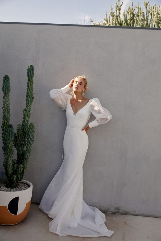 a sexy minimalist sheath wedding dress with a deep neckline, sheer puff sleeves and a train for a modern bride