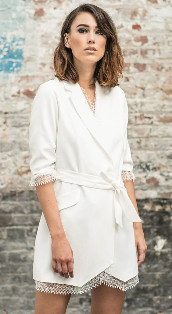 a white blazer mini wedding dress with a lace edge, short sleeves, a sash and statement accessories for a city hall wedding