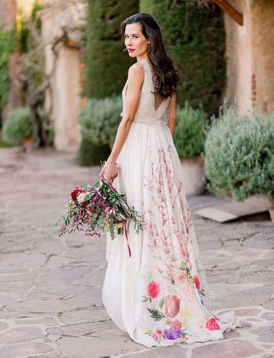 an A-line sleeveless wedding dress with an open back, colorful blooms on the skirt and a train for a summer bride