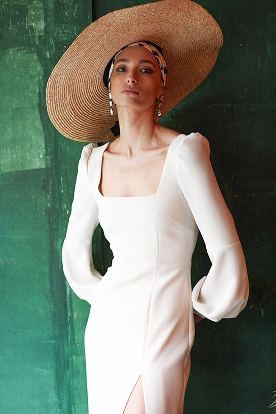 a minimalist sheath plain wedding dress with a square neckline, slightly puff sleeves and a front slit