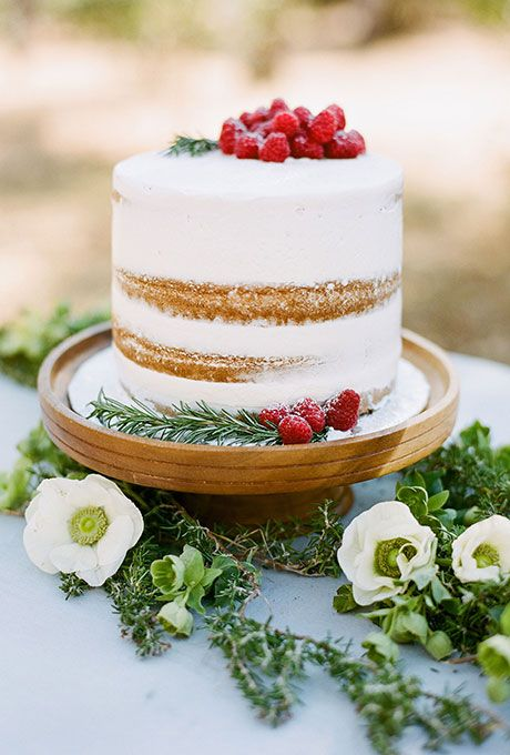 a naked wedding cake with fresh raspberries and greenery is a pretty wedding dessert to rock in winter