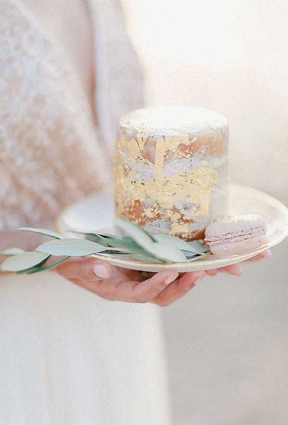 a naked wedding cake with gold leaf is a simple and tiny piece that looks chic and beautiful