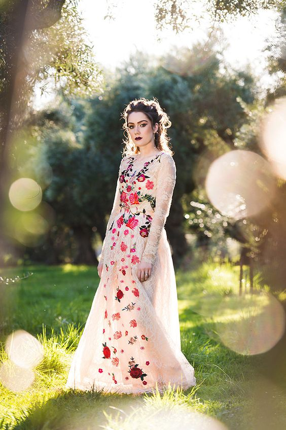 a lace A-line wedding dress with colorful floral embroidery, long sleeves paired with a dark lip for a statement summer or fall wedding