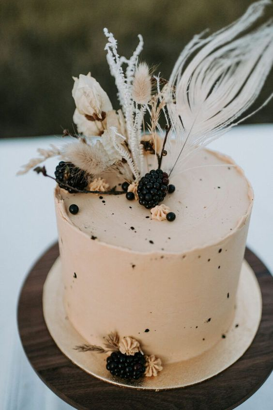 a neutral buttercream wedding cake with speckles, blackberries and dried blooms and grasses