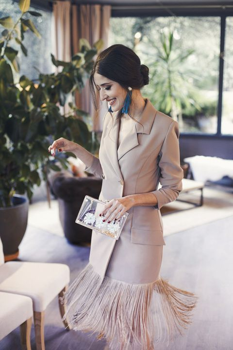 a tan blazer midi dress with long fringe, navy tassel statement earrings, a clear clutch with dried blooms for a non-typical bride