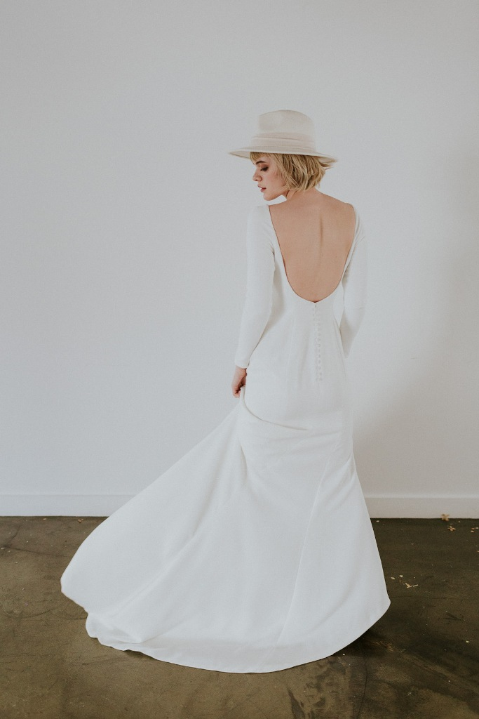 a minimalist A-line plain wedding dress with long sleeves and a cutout back plus a train and a neutral hat