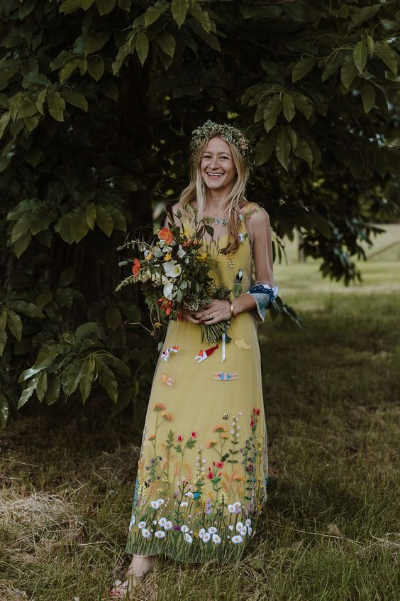 a mustard wedding dress with colorful floral embroidery, sheer sleeves, a floral crown and slippers for a forest nymph look