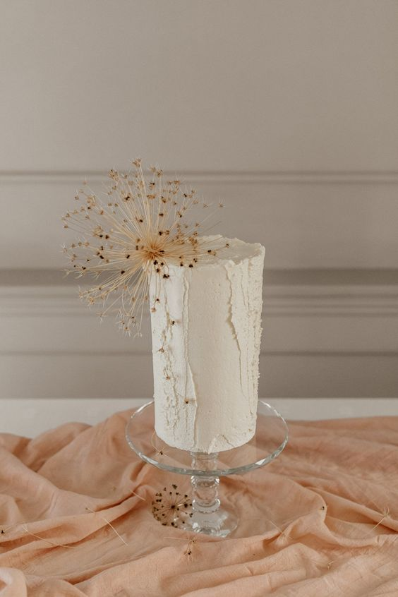 a neutral buttercream wedding cake with texture and dried blooms is a very stylish and refined idea to go for