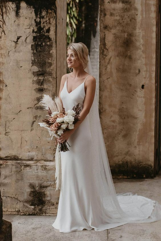 a classic slip wedding dress is a very minimal option, and it's always in trend, accessorize it with a cool veil