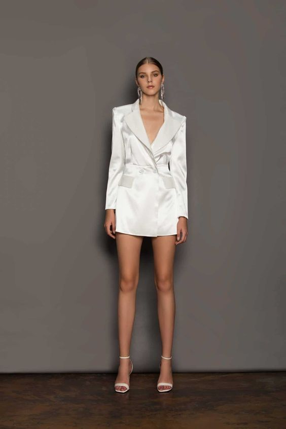 a satin blazer mini dress, statement earrings and white ankle heels for a bold and modern bridal look