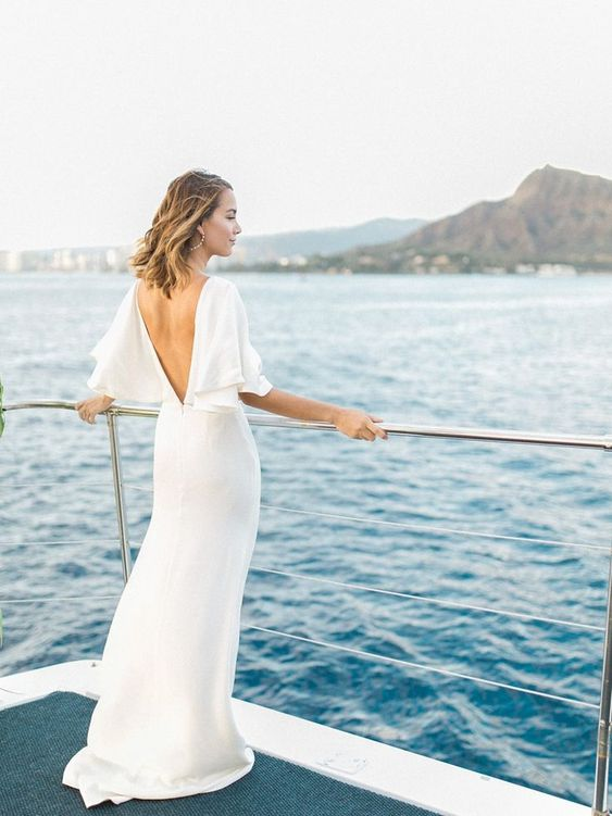 a minimalist sheath wedding dress with a deep V cut back and bell sleeves plus a slight train is super cool