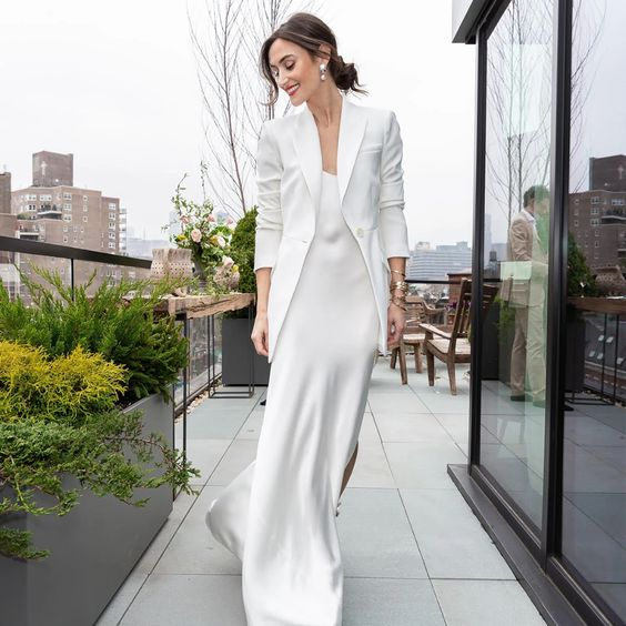 a classic slip wedding dress paired with a matching blazer and with statement earrings for a modern and simple bridal look