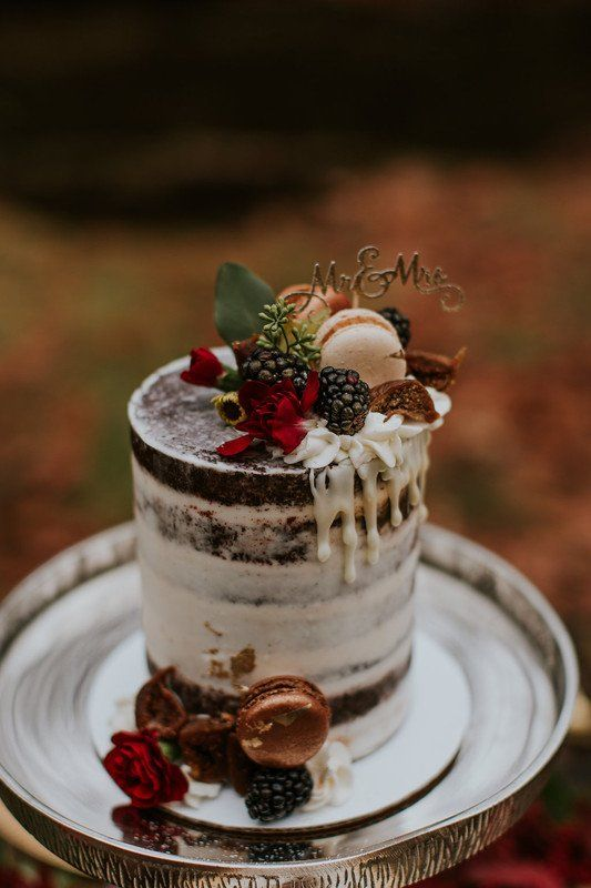 a pretty fall chocolate naked wedding cake with creamy drip, blackberries, macarons, figs, red blooms and a gold calligraphy topper