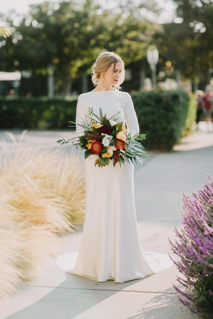 a minimalist plain sheath wedding dress with a high neckline, long sleeves and a train plus a cutout back