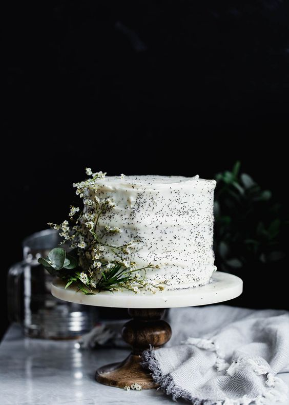 a pretty lemon poppyseed wedding cake decorated with white blooms and greenery is a lovely spring or summer idea