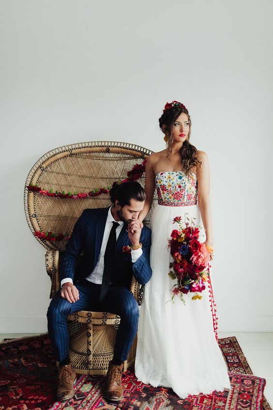 a strapless A-line wedding dress with a colorful floral bodice and a neutral skirt with a lace edge for a bold and fun wedding