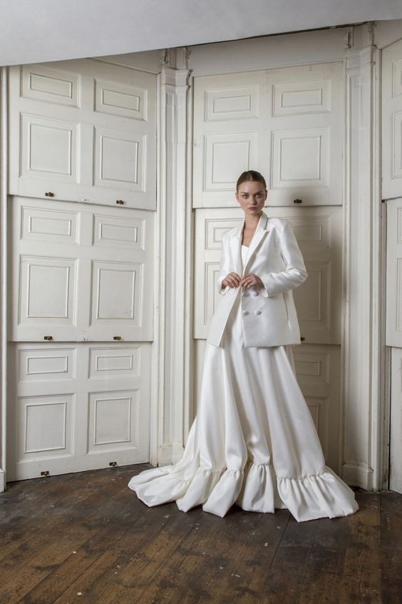 a minimalist A-line wedding dress with a slight train, an oversized white blazer on top for a trendy look