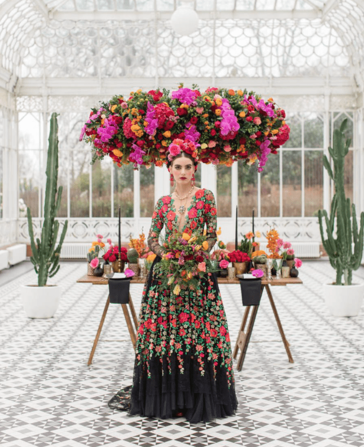 a statement black A-line wedding dress with colorful floral embroidery, a plunging neckline and a layered skirt plus layered necklaces for a Mexican wedding