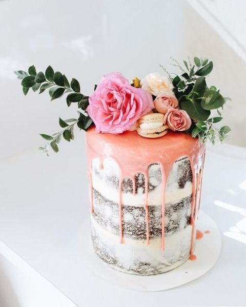 a small chocolate naked wedding cake with pink drip, pink and neutral blooms, macarons and greenery is delicious