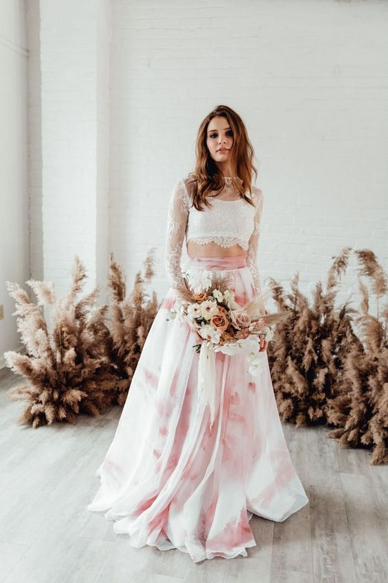 a trendy modern bridal separate with a white lace crop top with long sleeves and a pink tie-dye A-line skirt