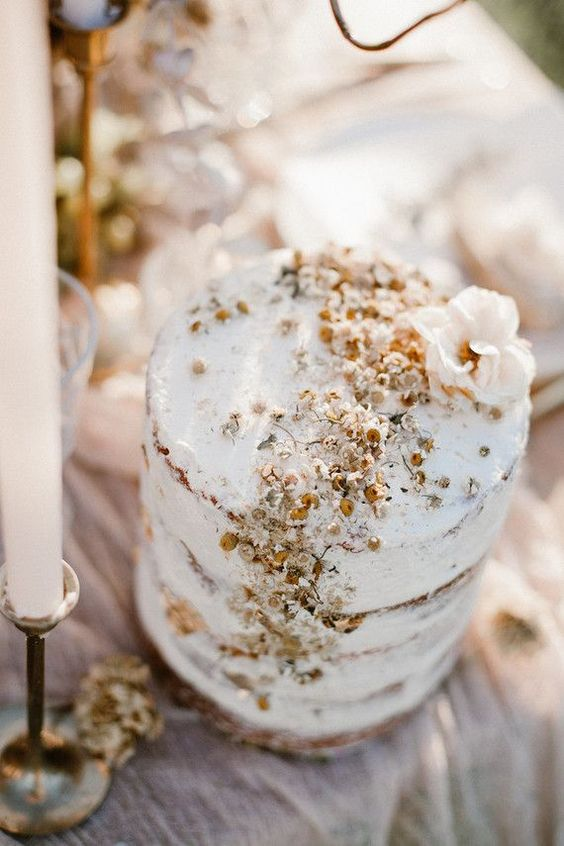 a small naked wedding cake with dried blooms on top is a lovely idea to go for, with a veyr trendy touch