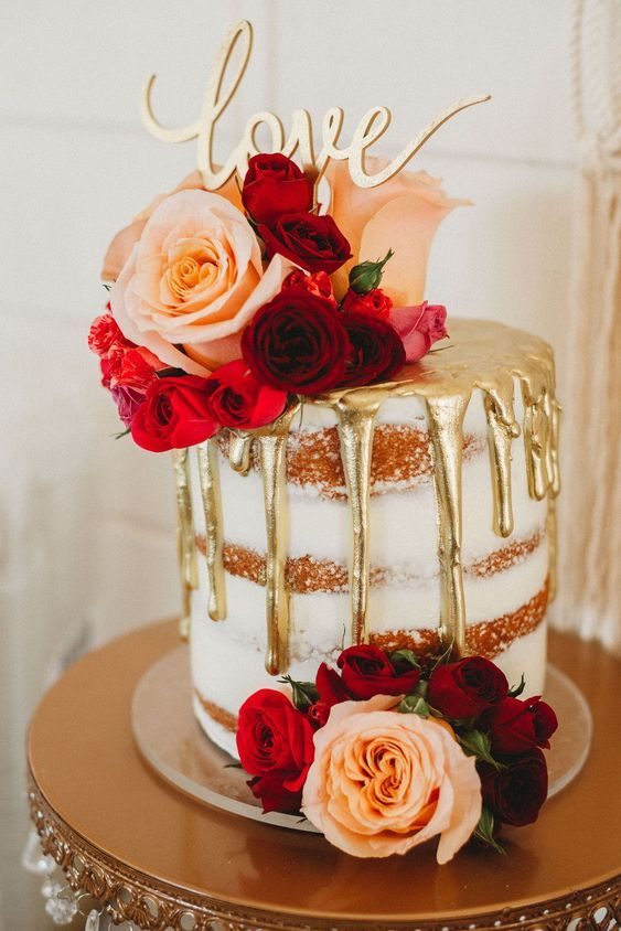 a small naked wedding cake with gold drip, pink, red and burgundy blooms, a gold calligraphy topper is utterly romantic