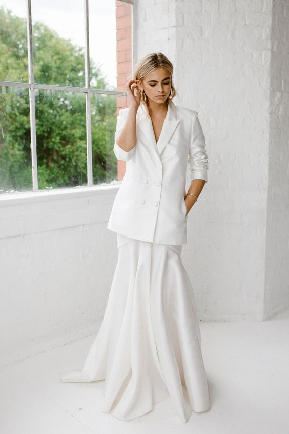 a stylish casual bridal look with a mermaid wedding dress and an oversized blazer over it to go outside if it's cold