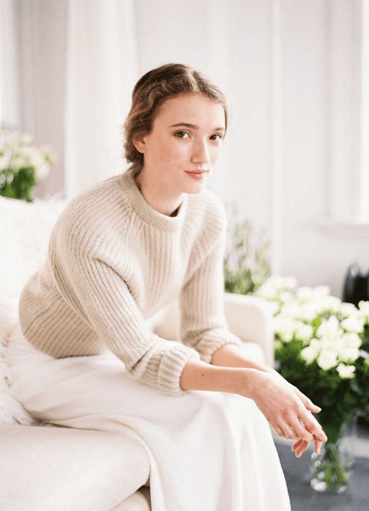 a casual bridal look with a white sheath skirt and a neutral sweater with a high neckline for a casual wedding
