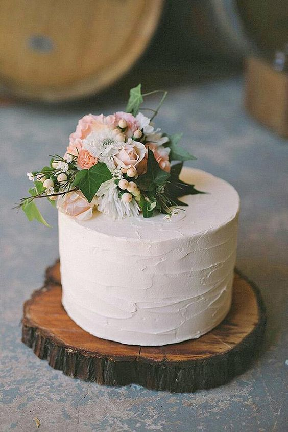 a small white buttercream wedding cake with pink and white blooms on top, some berries and greenery served on a wood slice