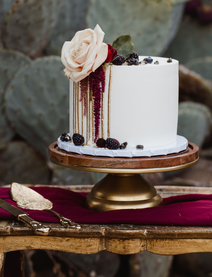 a small white wedding cake with gold drip, blackberries, leaves and blush and red blooms is veyr refined