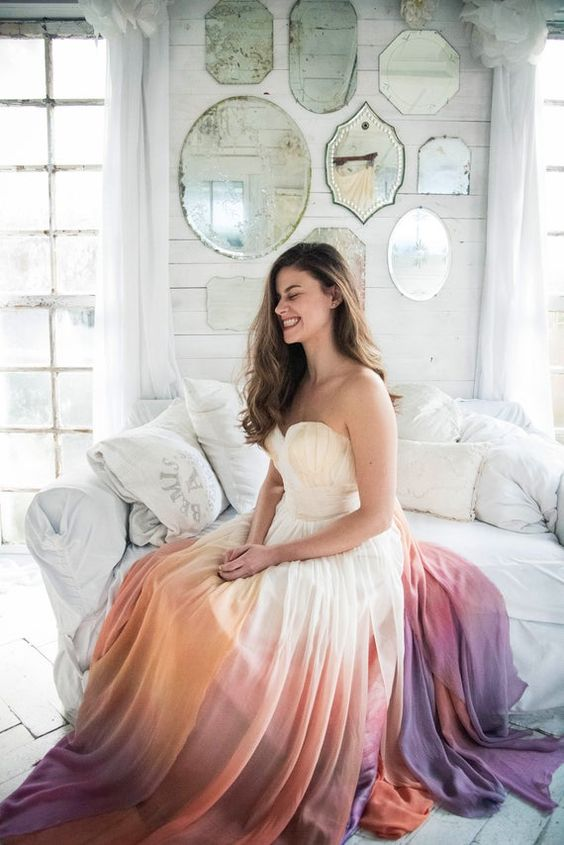 a strapless A-line wedding dress with a draped bodice and a bright ombre skirt plus a train is a very chic idea