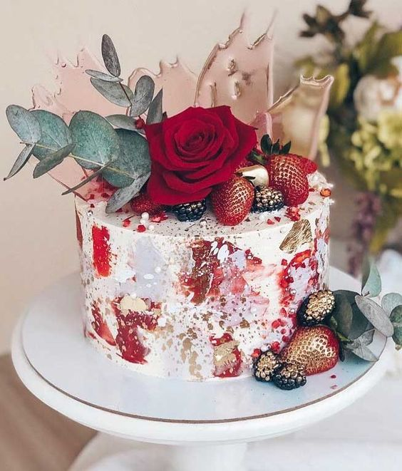 a unique wedding cake with red brushstrokes and gold leaf, gilded berries, a red rose, eucalyptus and pink sugar shards