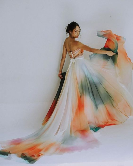 a strapless and bold watercolor wedding dress with a long train and a sash is a bright and cool idea for spring or summer