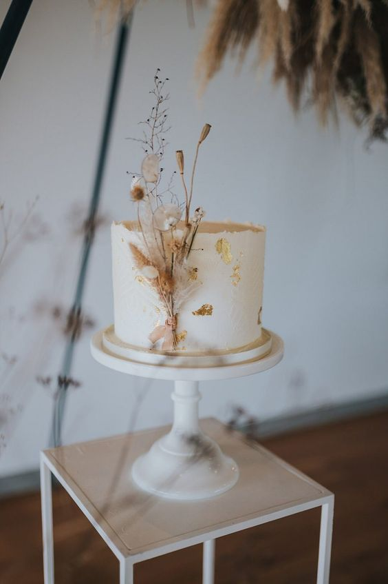 a white buttercream wedding cake decorated with gold leaf and dried blooms is a very refined and chic idea
