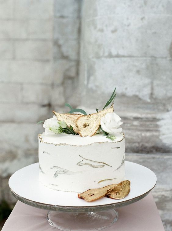 a white buttercream wedding cake with gold brushstrokes, gilded pears and white blooms for a fall celebration