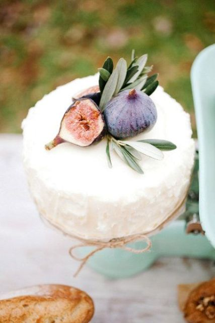a white textural buttercream wedding cake topped with figs is a lovely idea for a cozy fall wedding