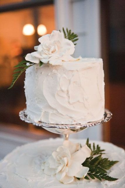 a white textural wedding cake with a white bloom and foliage is a timeless and refined idea to try