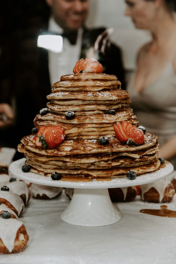 a pancake wedding cake with drip and fresh berries is a delicious alternative to a usual wedding cake